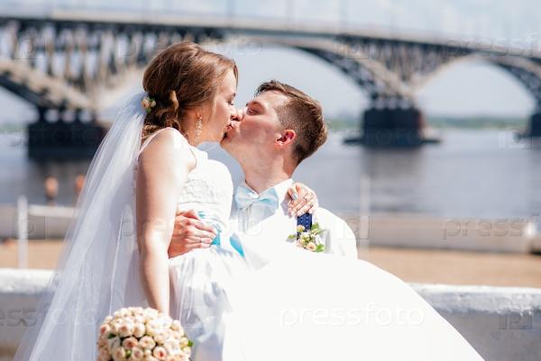 Жених и невеста фотографируются на фоне моста