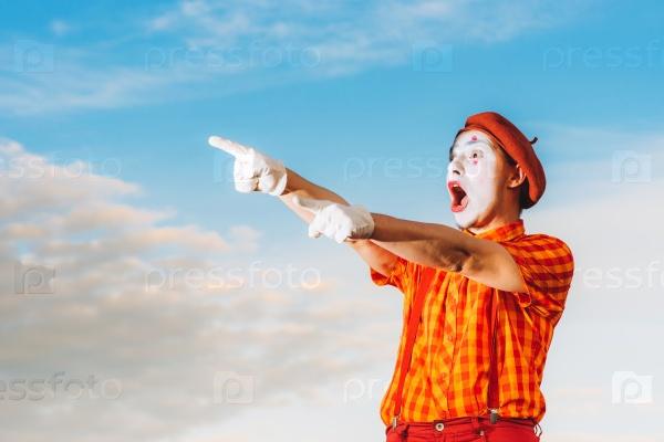 Мим показывает пантомиму на фоне голубого неба