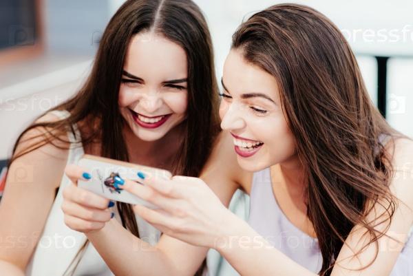 Девушки с телефоном в кафе