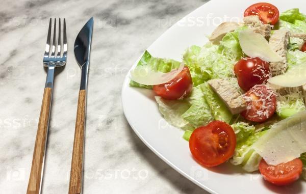 Салат из свежих овощей на белой тарелке