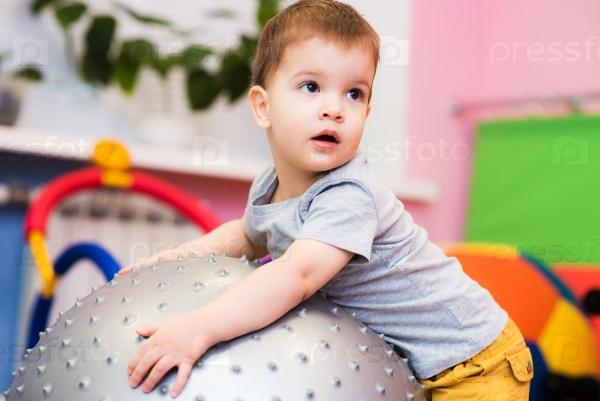 Маленький ребенок играет с фитболом