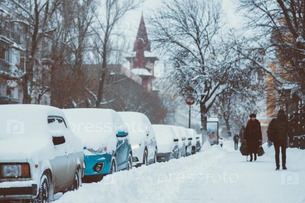 Автомобили паркуются вдоль дороги, покрытые снегом