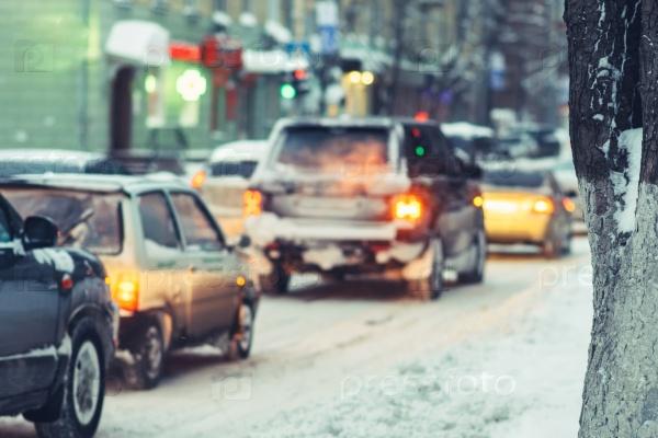 Автомобили идут на заснеженной дороге вечером