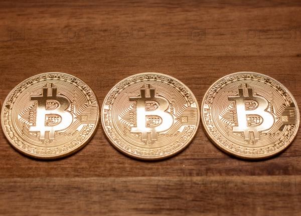 Три золотые монеты Bitcoin
