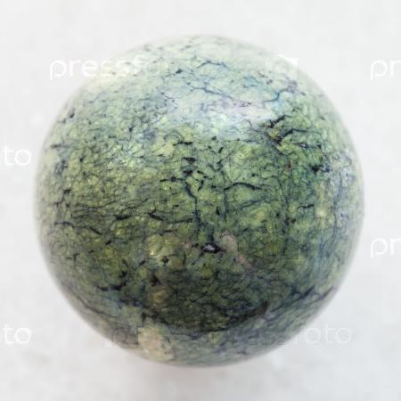 Шарик из змеиного камня на белом мраморе