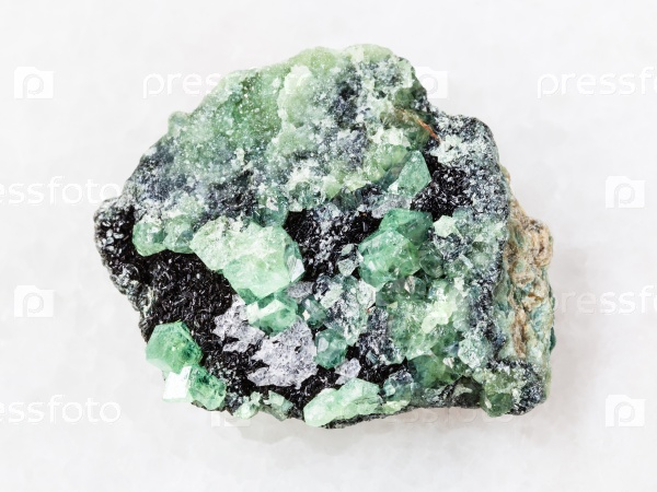Грубые кристаллы демантоида камня на белом