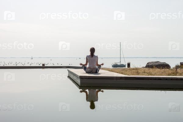 Женщины на берегу моря медитирует