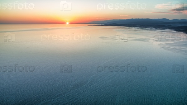 Вид с высоты на яркий закат над морем