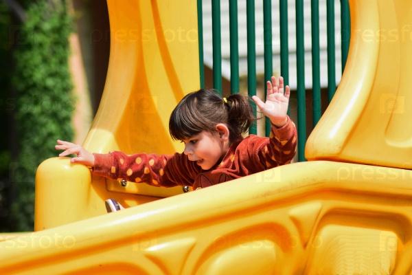 Маленькая шалунья играет на детской площадке в городском парке