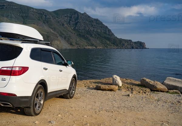 Большой белый автомобиль у моря
