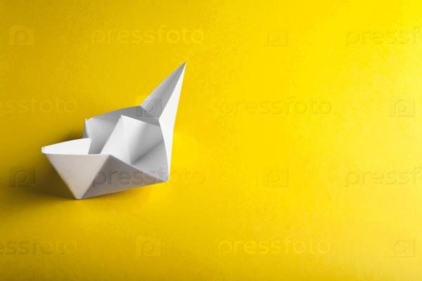Лодка из бумаги на желтом фоне