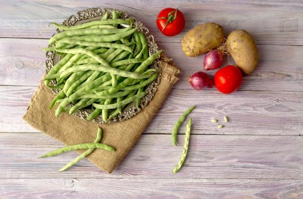 Зеленые бобы и овощи на деревянном фоне