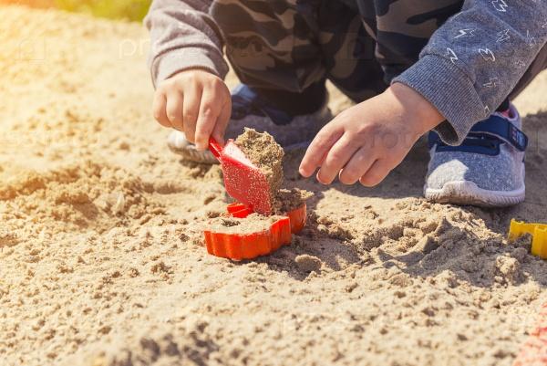 Руки ребенка в песке