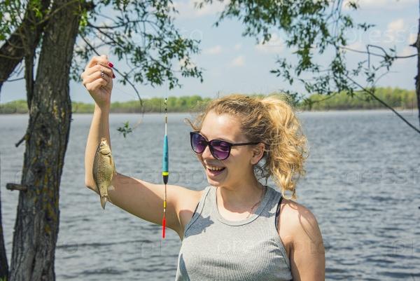 Девушка держит выловленную рыбу