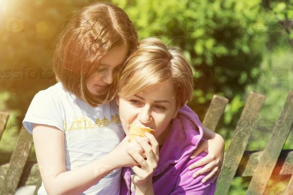 Дочь и мама обнимаются на солнце