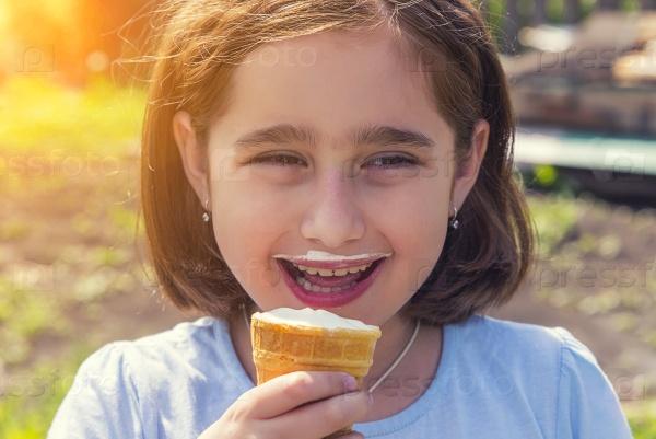 Девочка ест мороженое в вафельном стаканчике