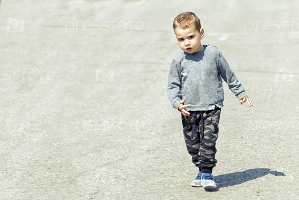 Маленький мальчик идет по дороге в одиночку