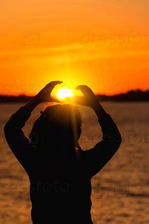 Силуэт девушки на фоне вечернего солнца