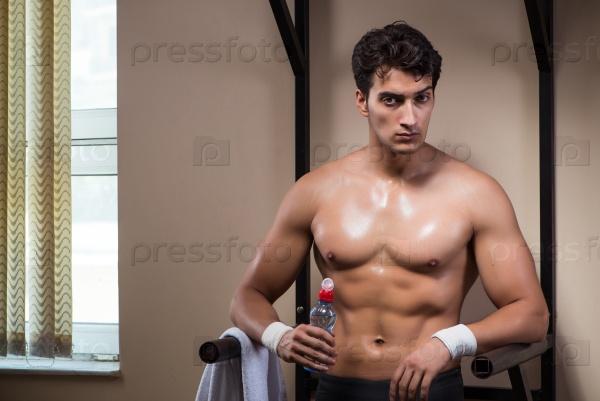Thirsty man drinking water in sports gym