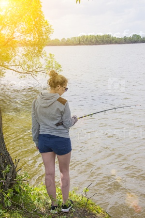 Девушка с удочкой рыбачит в пруду