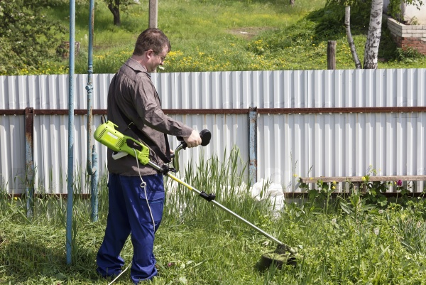 Человек косит траву во дворе