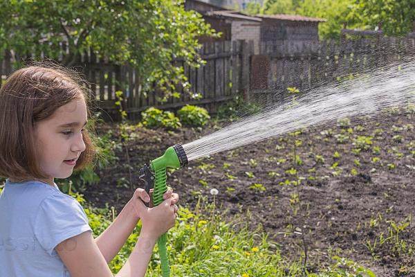 Девочка поливает сад из шланга