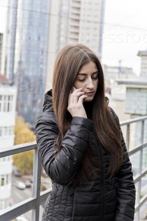 Женщина разговаривает по мобильному на балконе