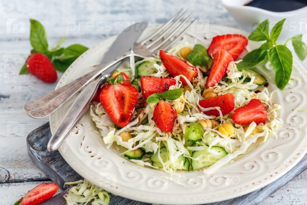 Salad with fresh strawberries and balsamic sauce.
