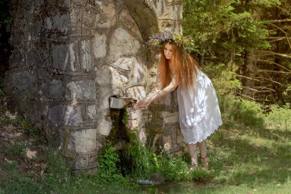 Молодая женщина возле источника в горах