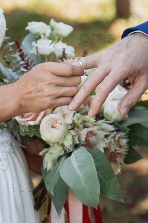 Невеста надевает кольцо на руку жениха