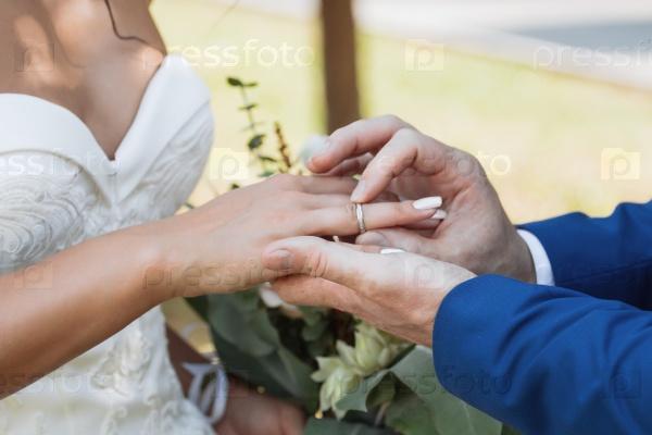 Жених надевает кольцо на руку невесты
