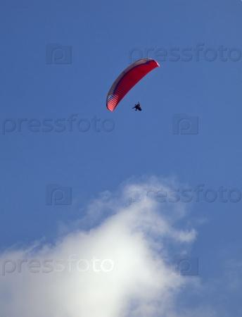 Парапланерист в синем небе