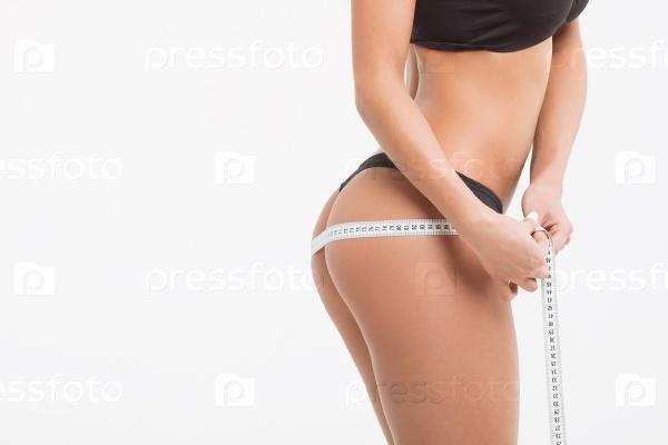 Молодая красивая девушка измеряет части тела