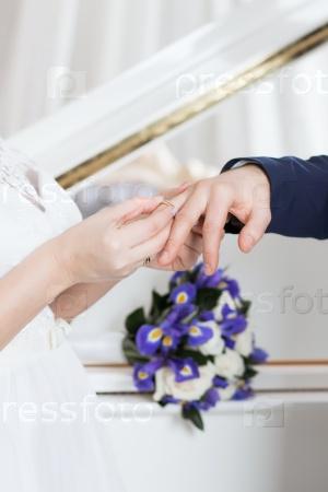 Невеста надевает кольцо жениху
