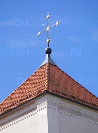Золотой крест на красной черепичной крыше