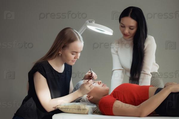 Молодая женщина, работающая на наращивании ресниц