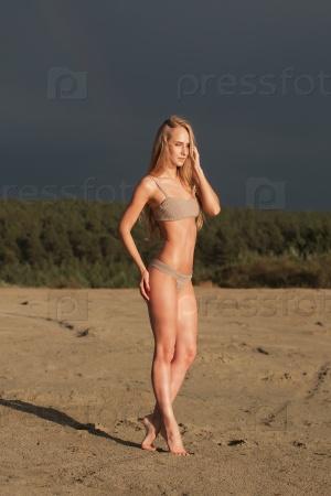 Девушка с идеальной фигурой в коричневом купальнике на пляже