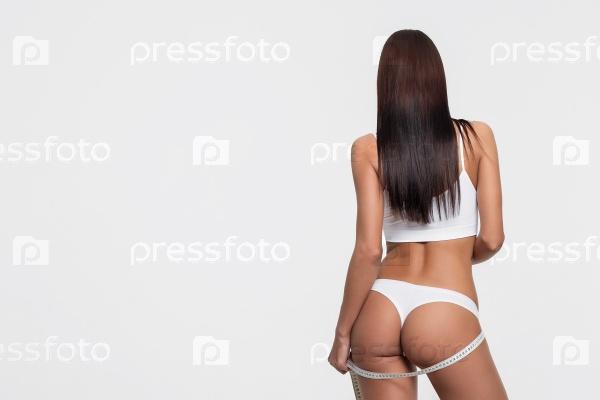 Молодая красивая девушка измеряет тело