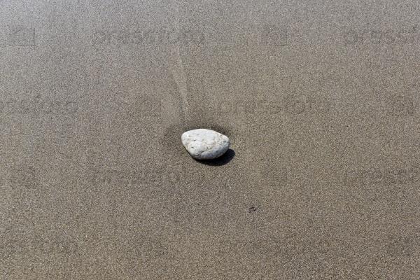 Одинокий камень на песке в прибое
